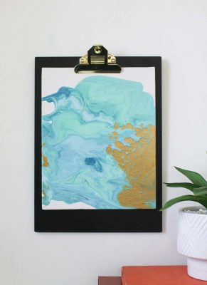 diy paint pour canvas art in aqua colors with gold and gold accents on a clipboard