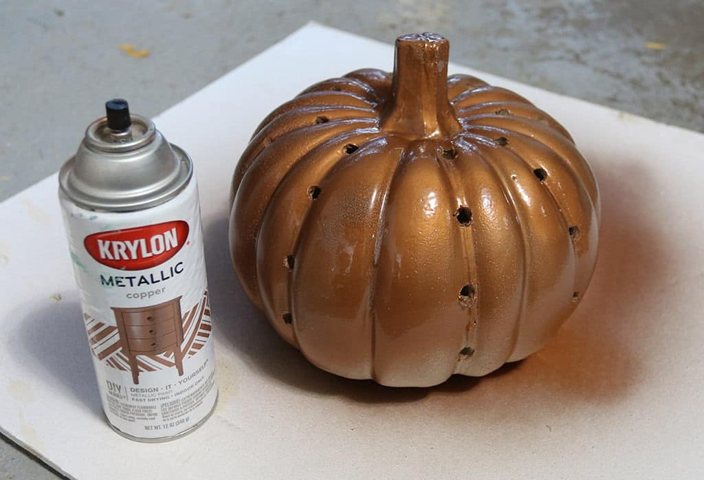 copper spray painted pumpkin with holes