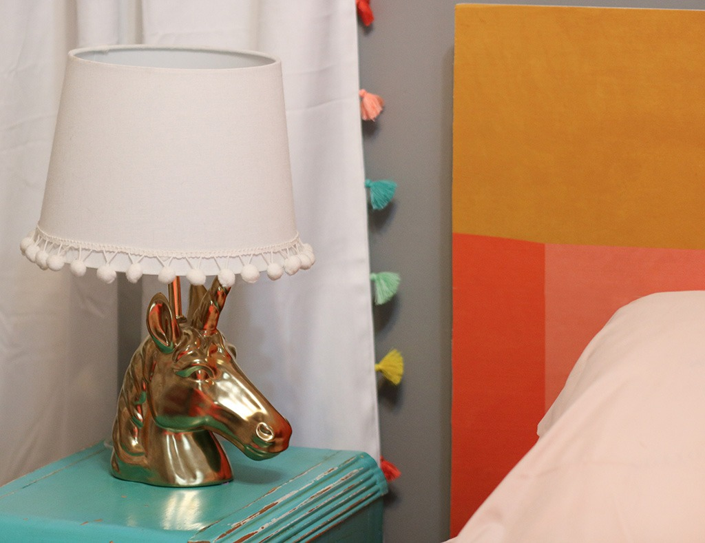 DIY colorful wallpapered headboard detail shot unicorn lamp
