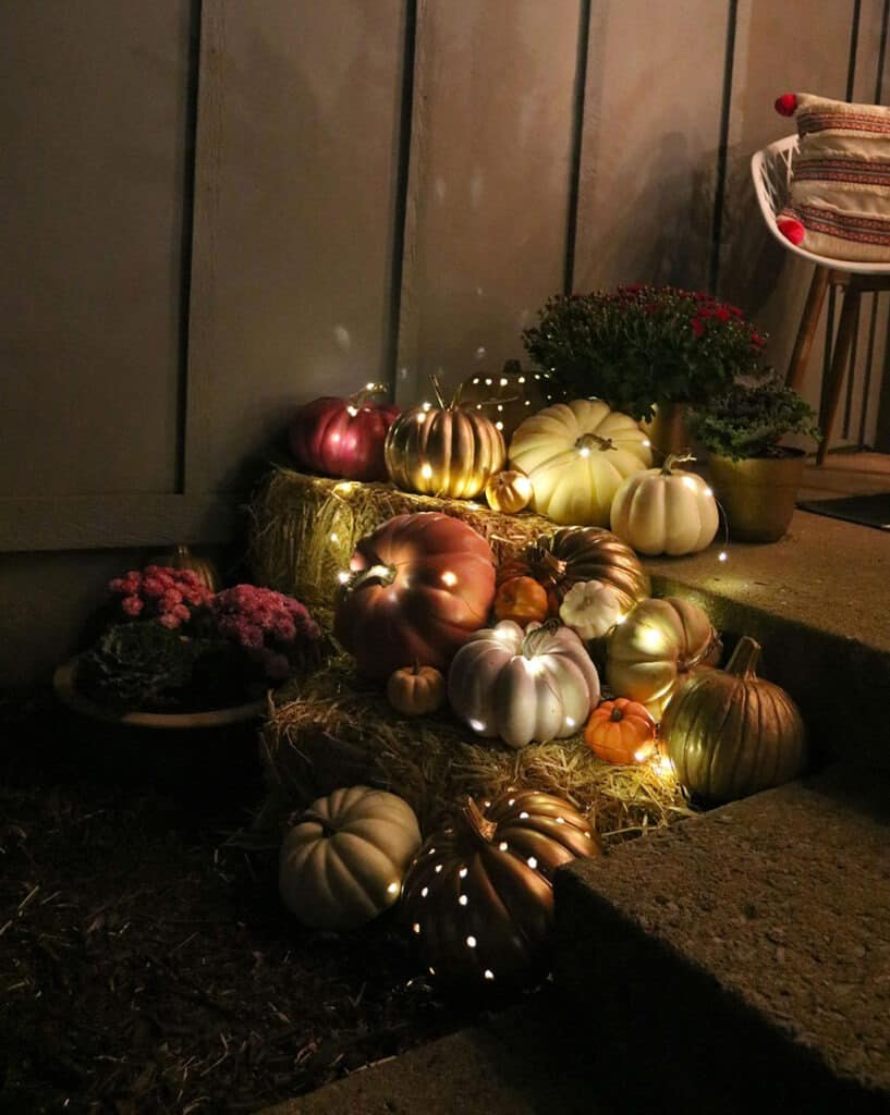 outdoor fall decor decor pumpkins, plants, and fairy lights at night