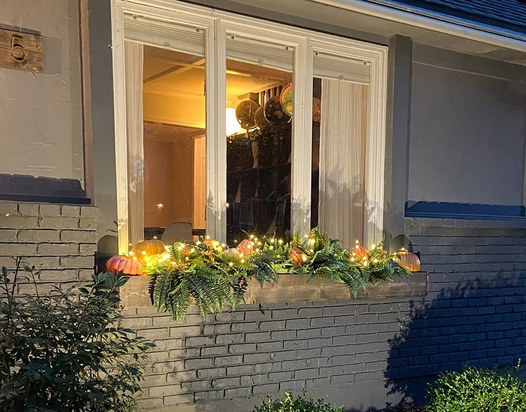 outdoor fall decor and window boxes with pumpkins and faux ferns