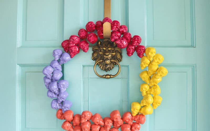 Learn how to make a DIY colorful and modern skull Halloween wreath that will look amazing on your front door this fall. So festive!