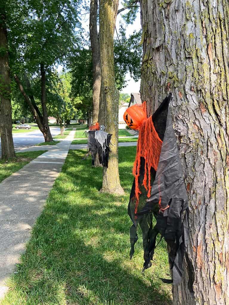 halloween ghouls in trees on sidewalk