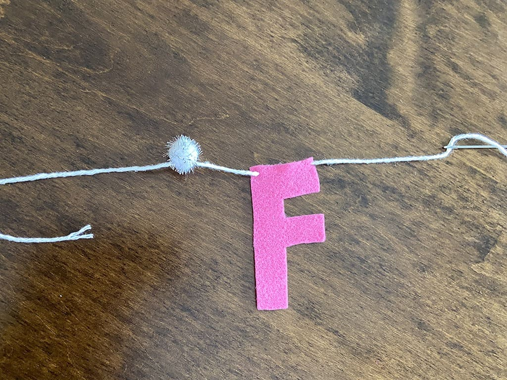 needle and yarn for stringing felt letters on a banner
