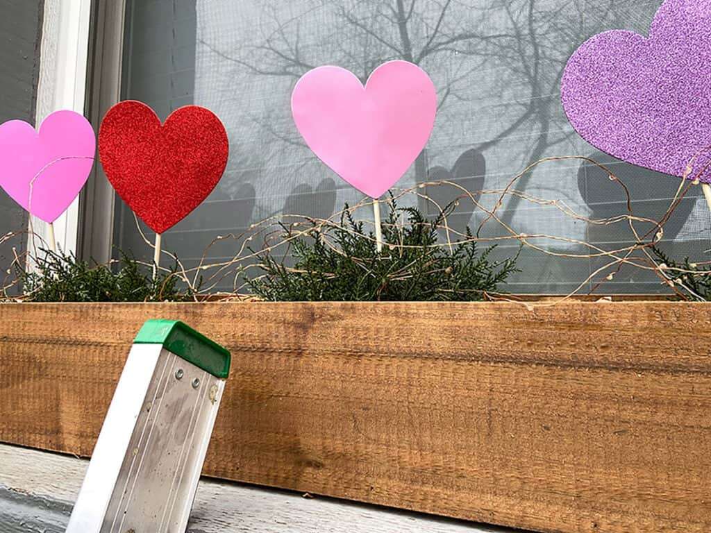 Foam heart picks in window box with fairy lights