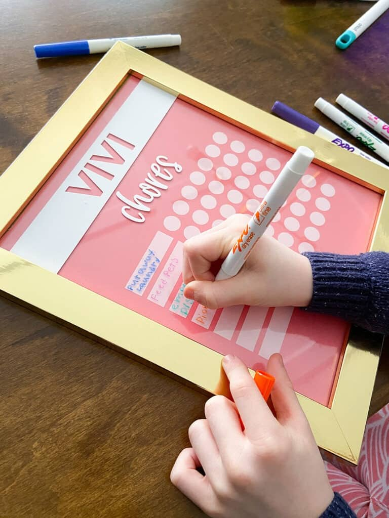Adding chores to a kids DIY chore chart with dry erase markers