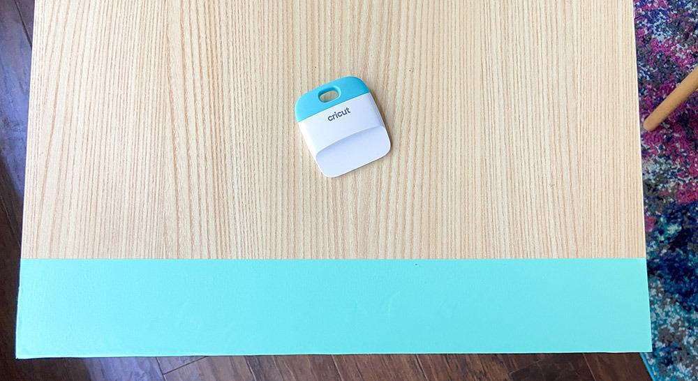 applying turquoise mint vinyl to a table top design with a burnishing tool and fingers