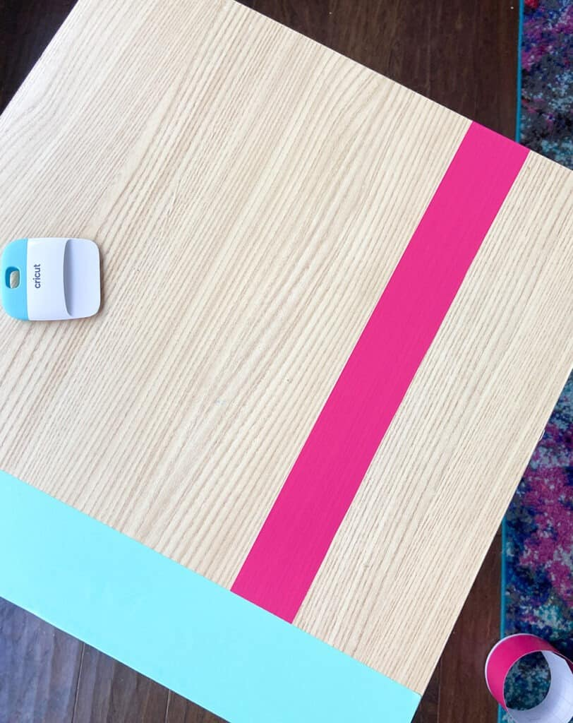 applying party pink vinyl to a table top design with a burnishing tool and fingers