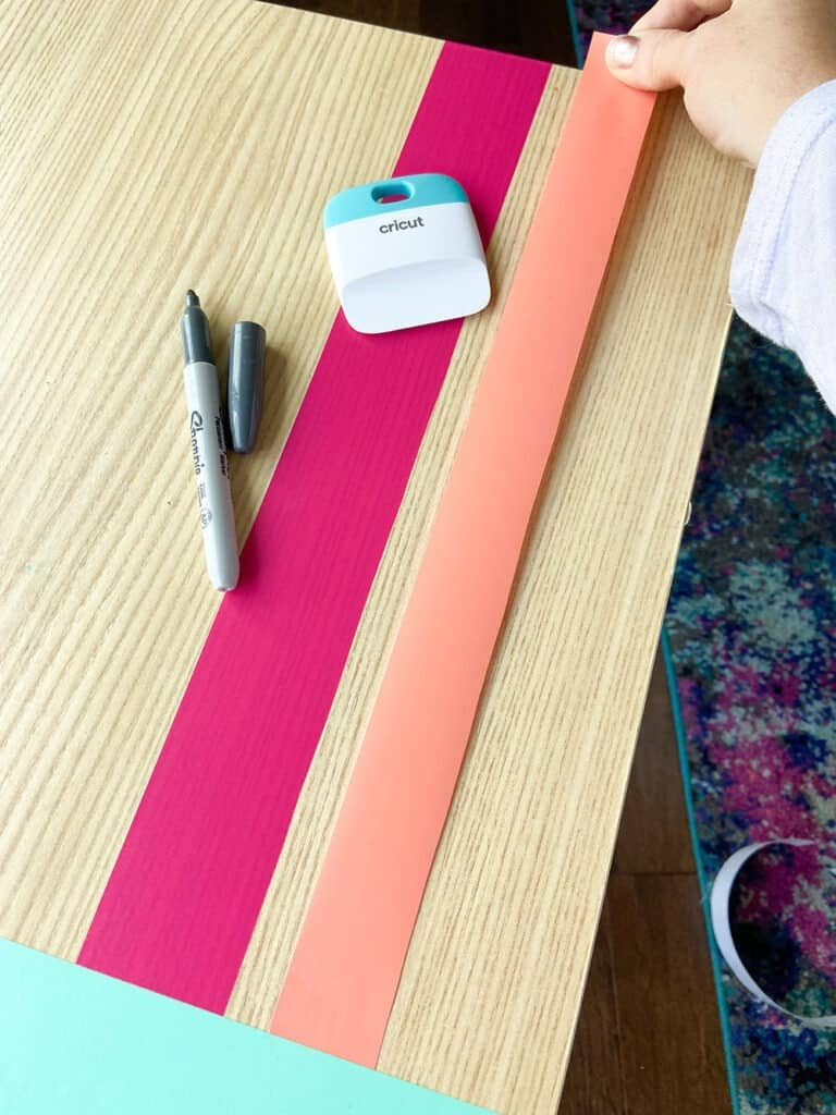 applying coral vinyl to a table top design with a burnishing tool and fingers