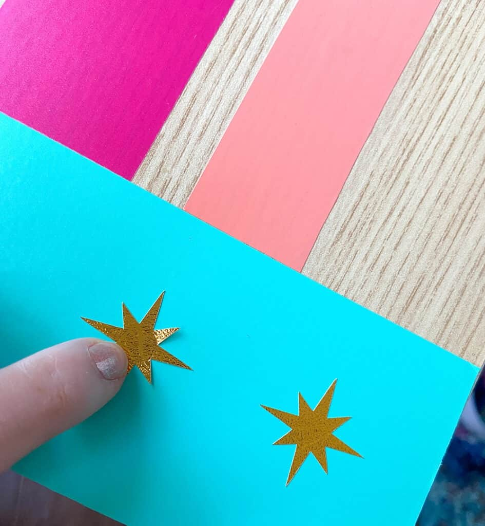 turquoise, hot pink, and coral vinyl design on a desk top with modern gold accents applying gold stickers over vinyl