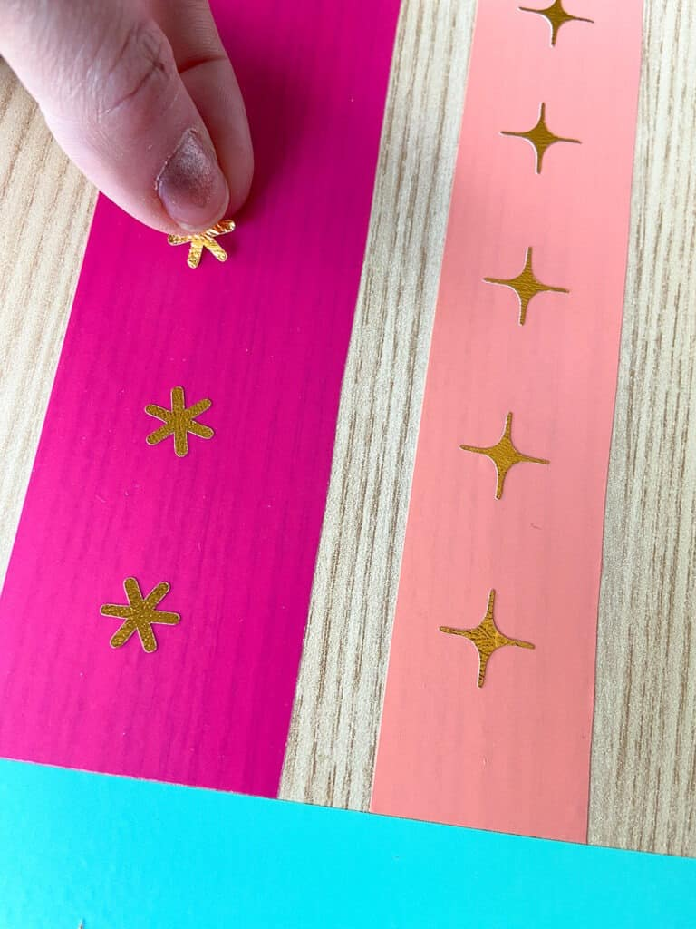 turquoise, hot pink, and coral vinyl design on a desk top with modern gold accents