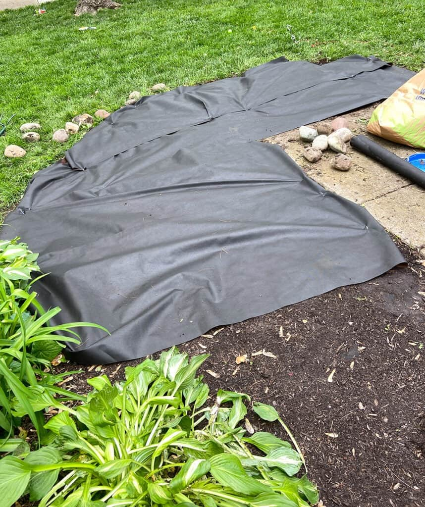tearing out overgrown weeds from landscaping, laying weed mat, and mulching
