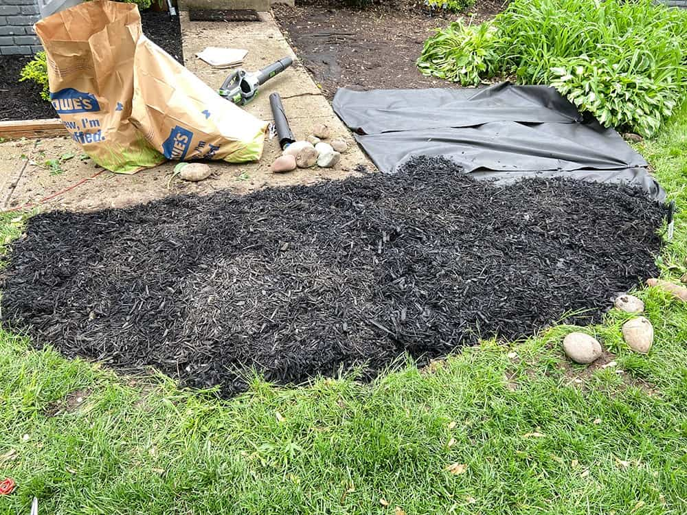 adding weed mat and mulch to landscaping beds