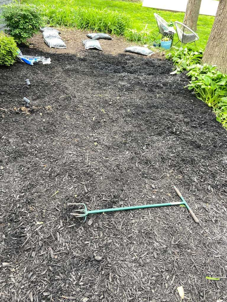 adding 45 bags of mulch to landscaping bed