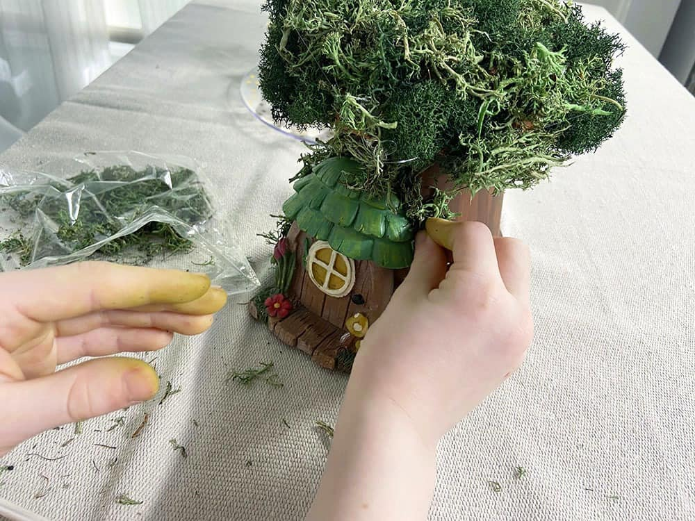 hot glue gnome doorway and moss to a terra cotta pot tree