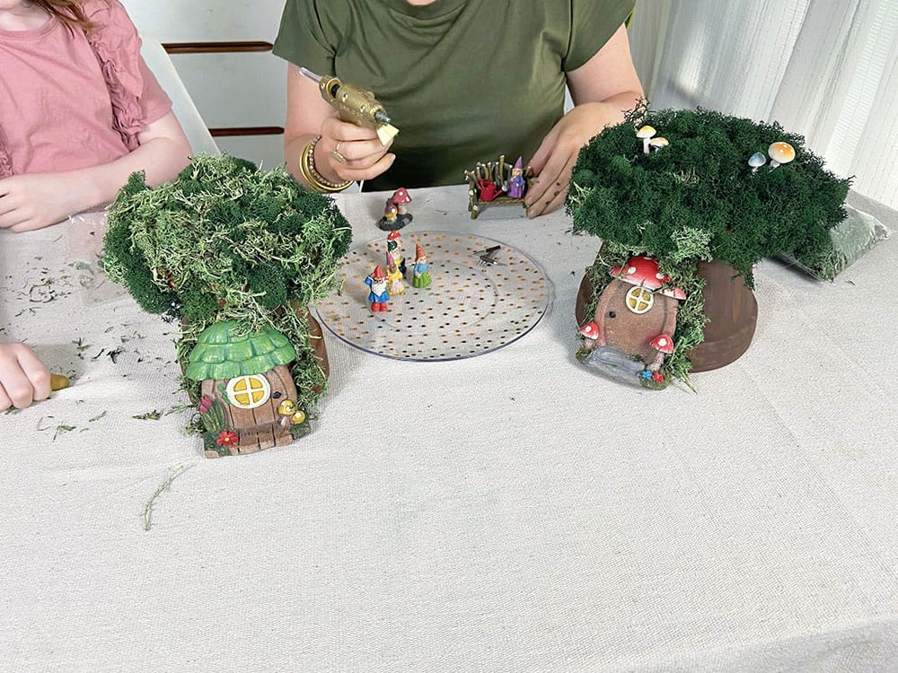 Hot gluing accessories to my DIY gnome garden house