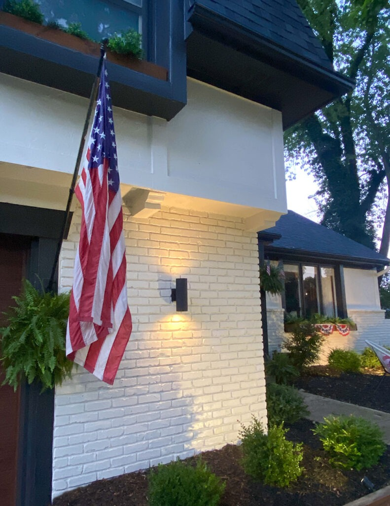 How a DIY wood cladding slat porch wall added some much needed warmth and curb appeal to our home! Get the full tutorial and product links. Exterior modern lights at night.