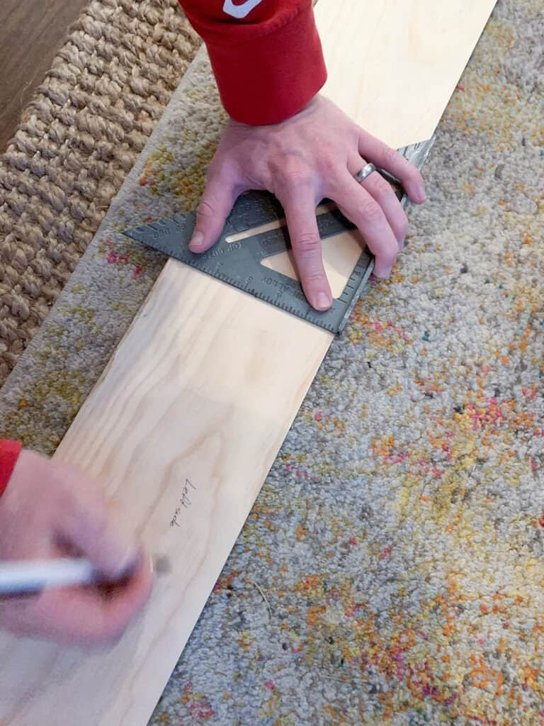 using a square to mark wood for cutting - fireplace makeover