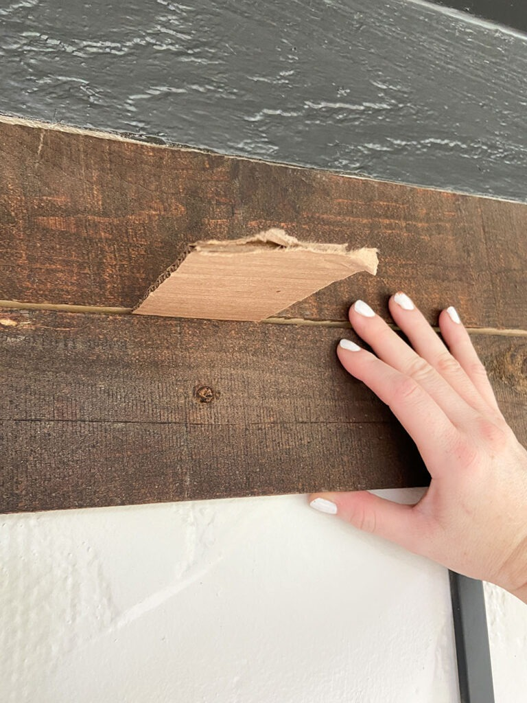 Installing wood slat to wall using a level, shim, and drill
