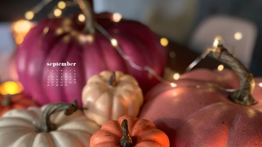 colorful stacked pumpkins on a table with fairy lights bokeh - pink, orange, coral, cream September 2021 - FREE wallpaper calendars in Sunday and Monday starts + no-calendar options. 35 designs for both desktop and smart phones!