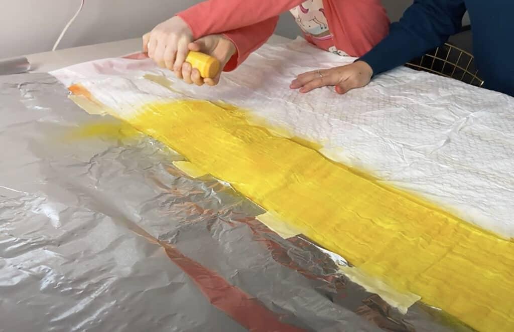 spray yellow tumble dye on muslin blanket