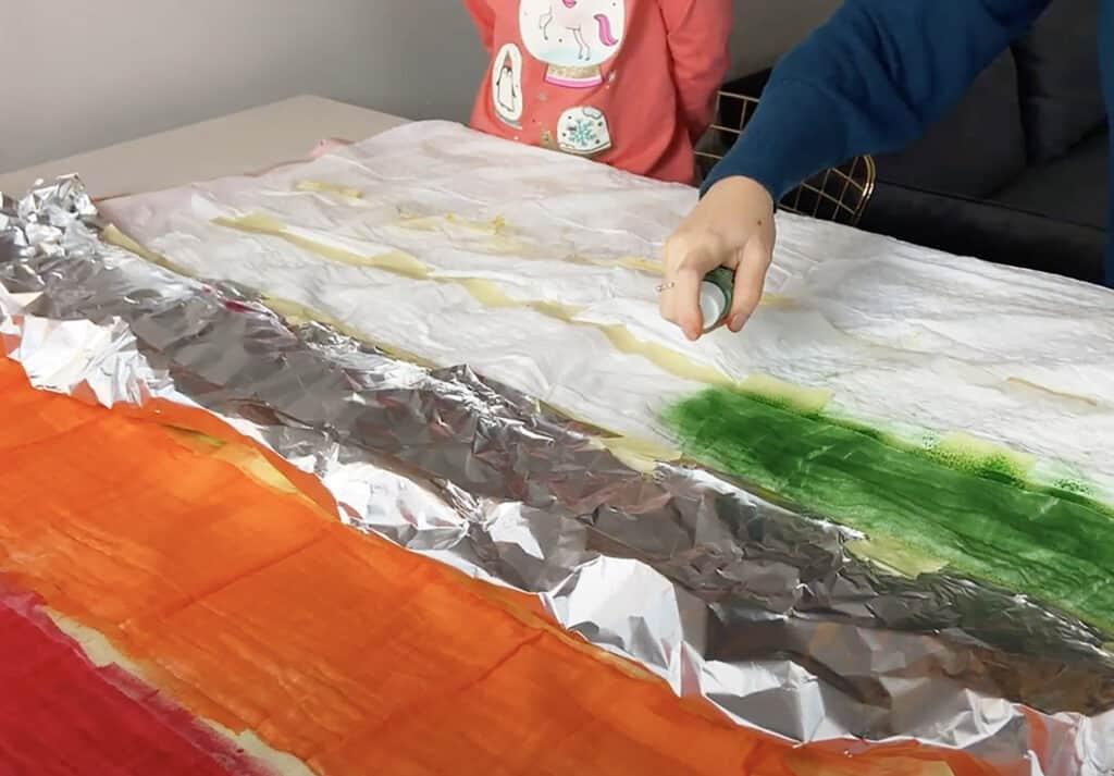 spray green tumble dye on muslin blanket