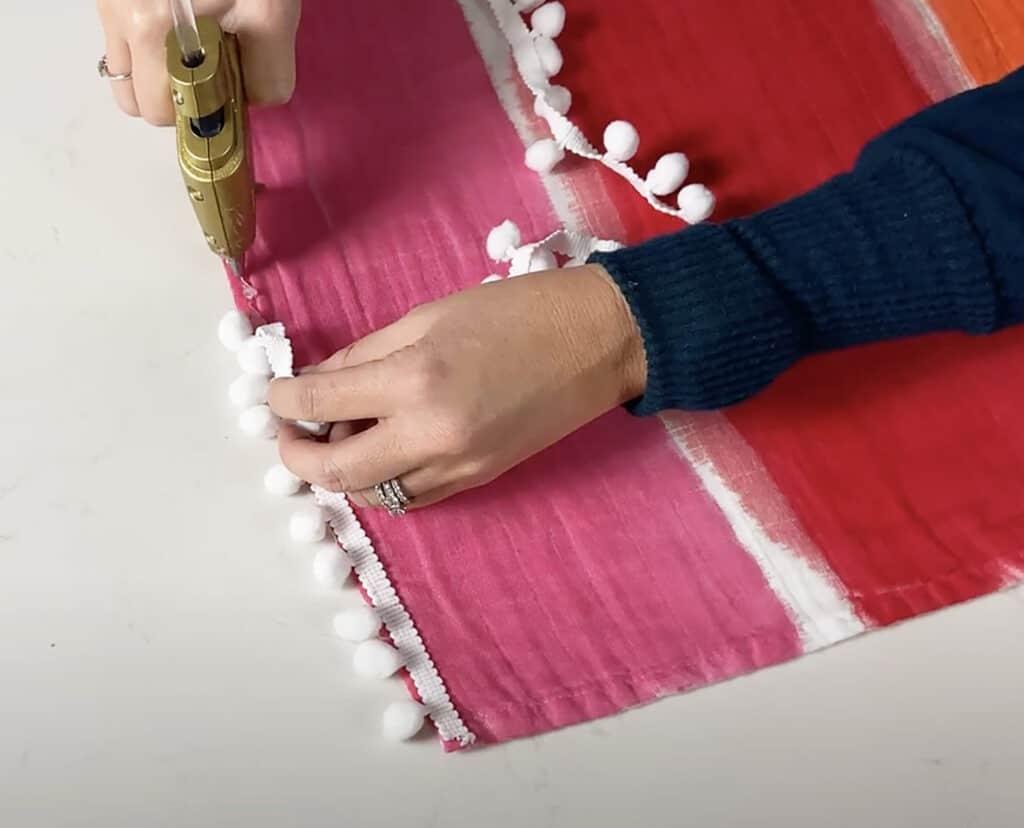 hot gluing pom pon trim ribbon to the blanket