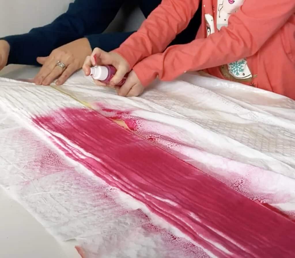 spray hot pink tumble dye on muslin blanket