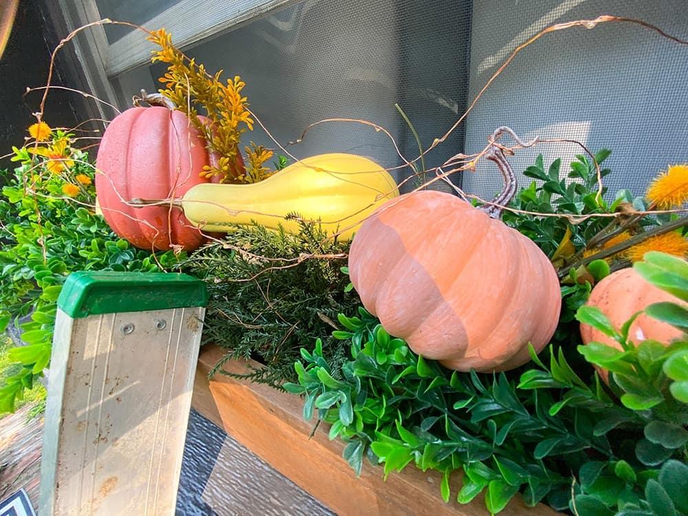 fall window box decor faux greenery, pumpkins, and fairy lights