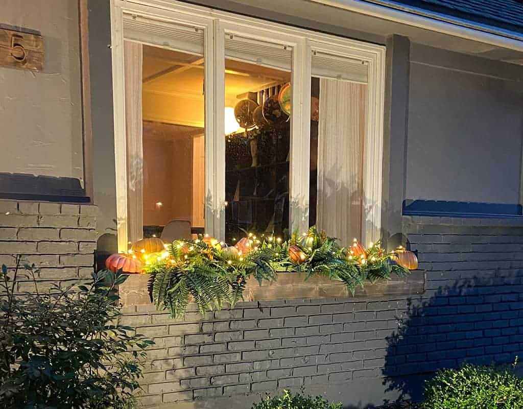 fall front porch and window boxes at night