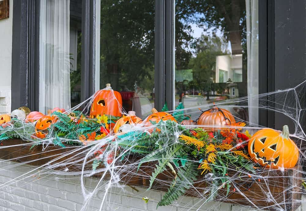 a window box full of light up pumpkins, skulls, and spiderwebs
