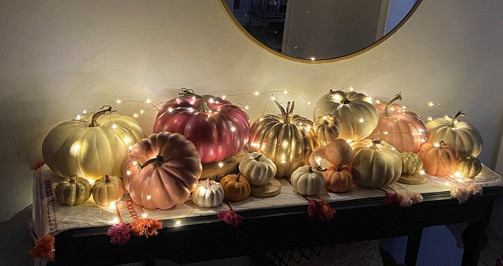 Fall entryway with lots of colorful pumpkins and fairy lights