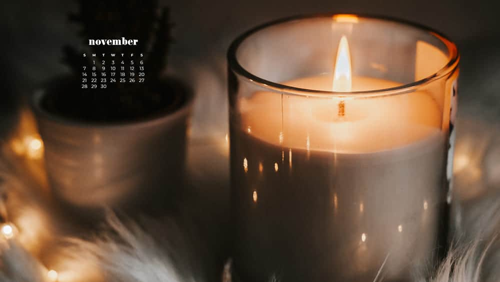 Cozy scene with a blanket, plant, and candle November - FREE wallpaper calendars in Sunday & Monday starts + no-calendar designs. 35 options for both desktop and smart phones!