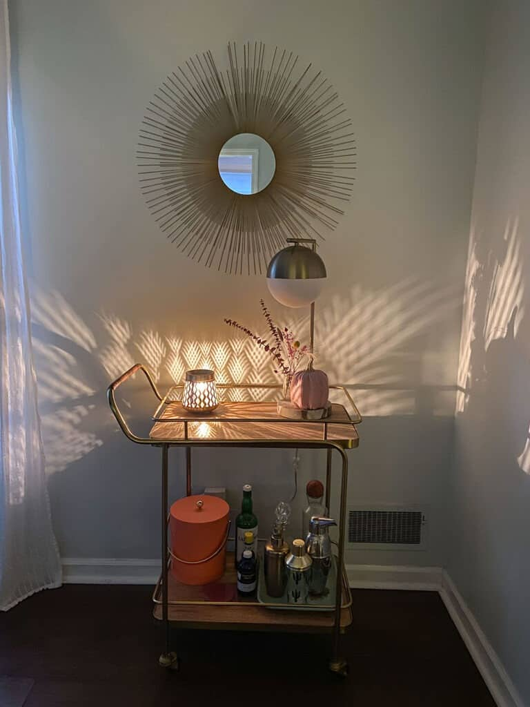 Gold and wood decorated bar cart with a faux pink pumpkin, dried florals in a vase, and a wax warmer that scatters light across the wall