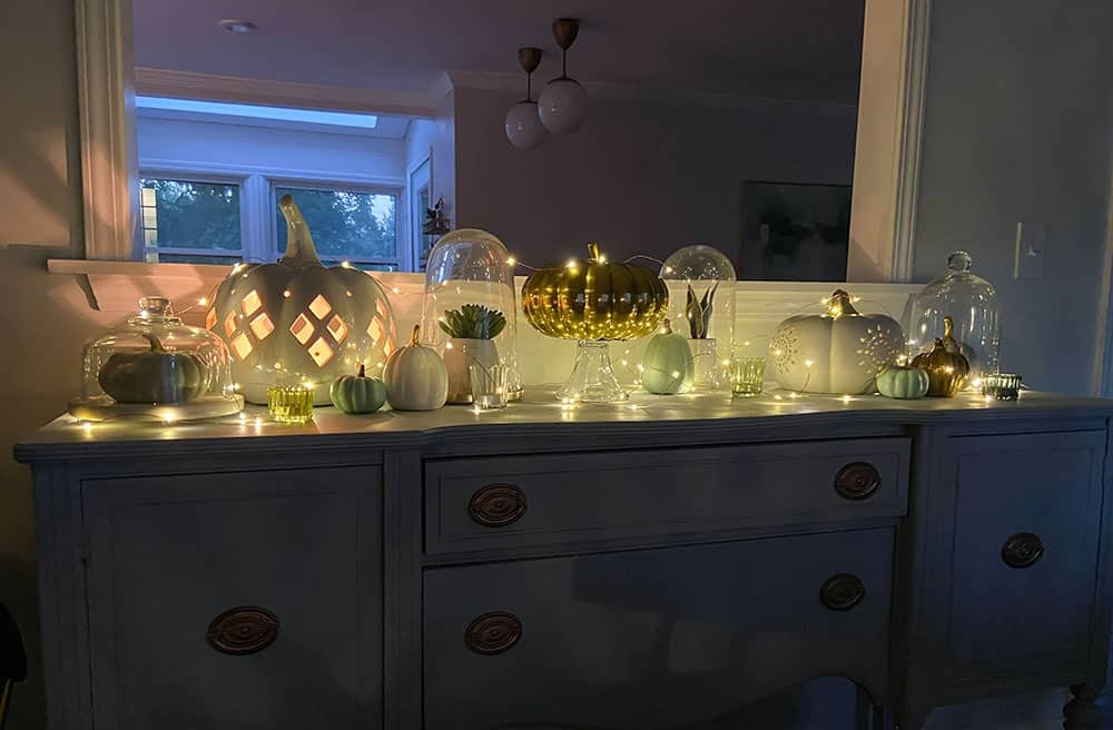 faux pumpkins, plants, glass cloches, candles, and fairy lights on a vintage cabinet top - easy fall decorating ideas!