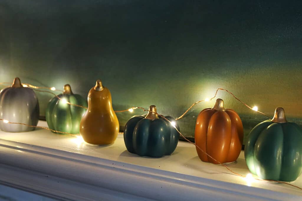 Fall decorating tips for your fireplace mantel using colorful faux pumpkins and fairy lights