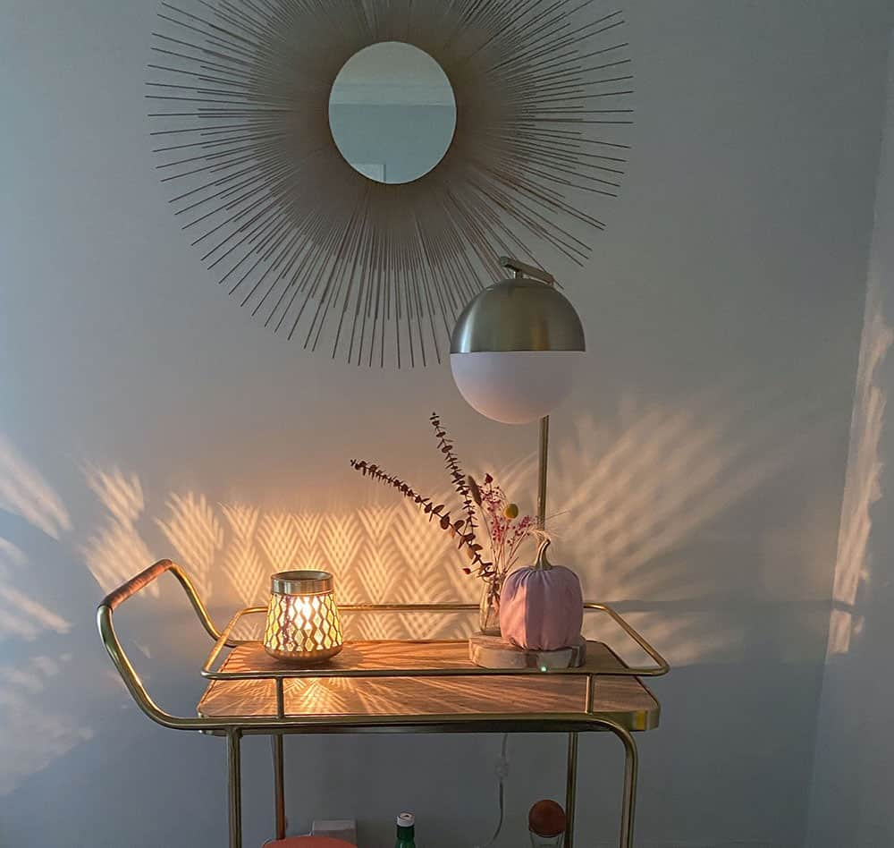 Gold and wood decorated bar cart with a faux pink pumpkin, dried florals in a vase, and a wax warmer that scatters light across the wall. fall decorating ideas!