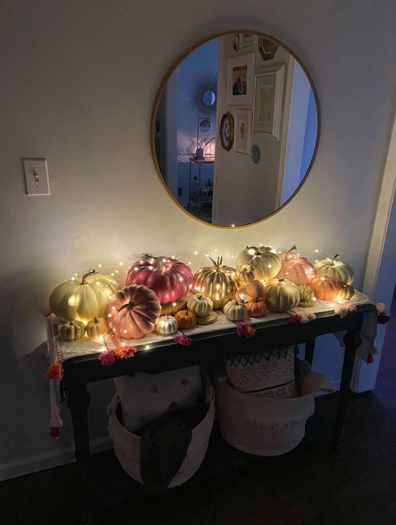 Fall entryway with lots of colorful pumpkins and fairy lights Fall decorating tips for inside your home — 4 easy decor ideas that make your home feel extra festive and cozy with all the hygge vibes!